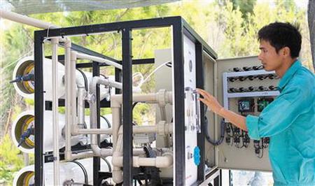 三沙市西沙洲工作人员正在调试海水淡化设备